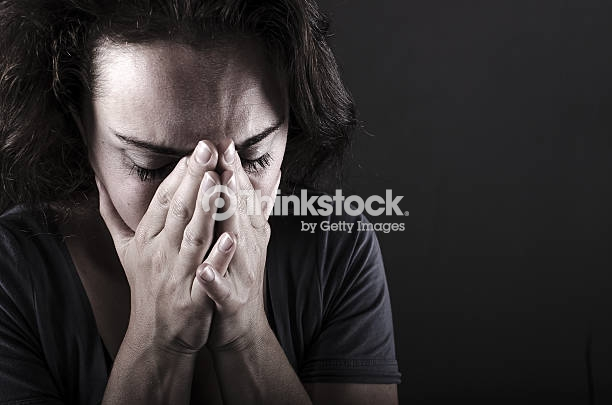 Depressed woman with hands over her face. Crying.